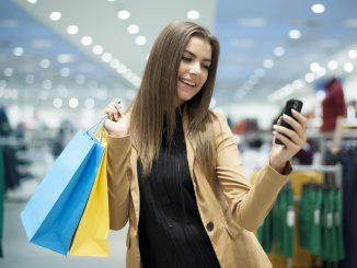 Young girl shopping with bags and cell phone in her hands
