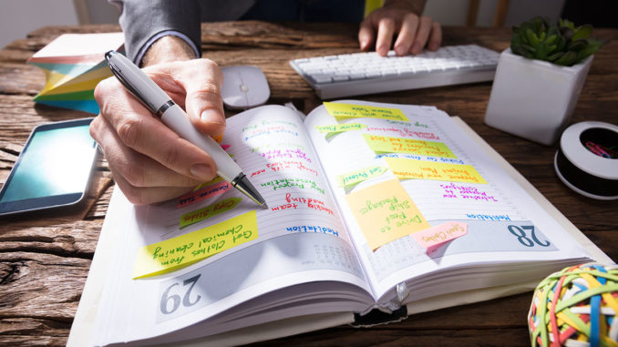 Lifelong Learning: Close-up Of A Businessperson's Hand Writing Schedule In Diary With Pen On Wooden Desk