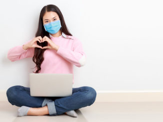Young Asian woman wearing surgical mask sits cross legged with a laptop on her legs on the floor and forms a heart with her hands
