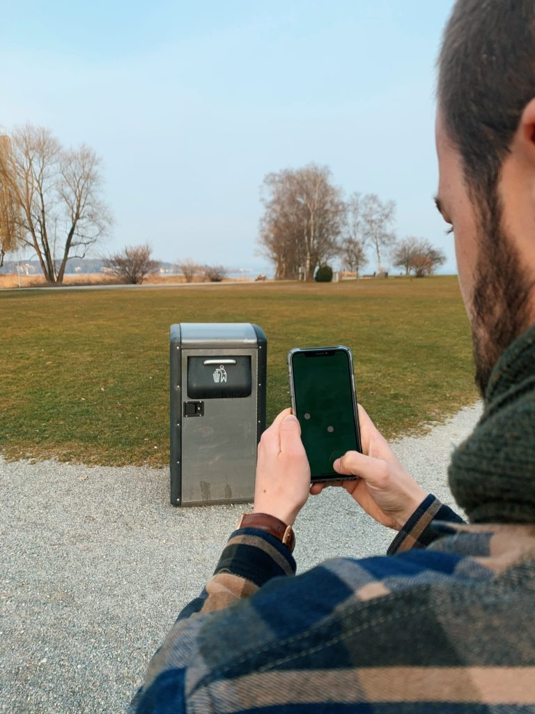 Pascal Ritter in Front of a Trash Can Using the App the Fortunate Planet