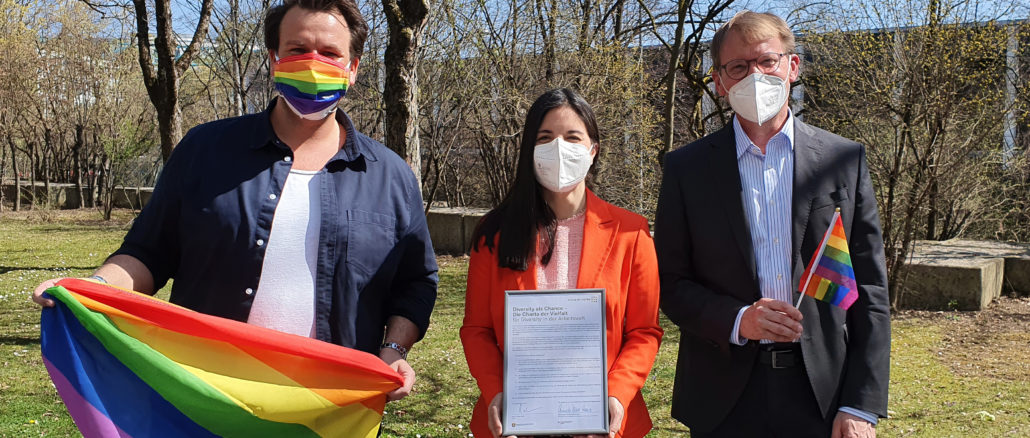 Christoph Schlottmann, Dr. Christine Menges and Prof. Dr. Stefan Baldi with the signed Diversity Charter and Pride flags in the MBS garden.
