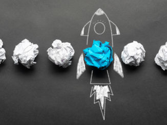 Crumpled paper balls and a rocket drawing on a blackboard.
