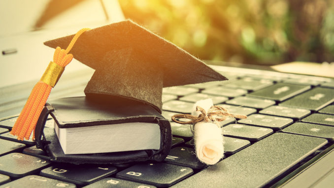 Graduate hat, scroll and book in miniature on laptop keyboard