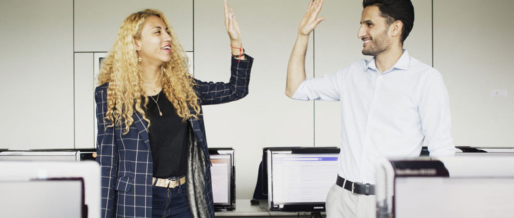 Two students high-fiving in the computer lab.